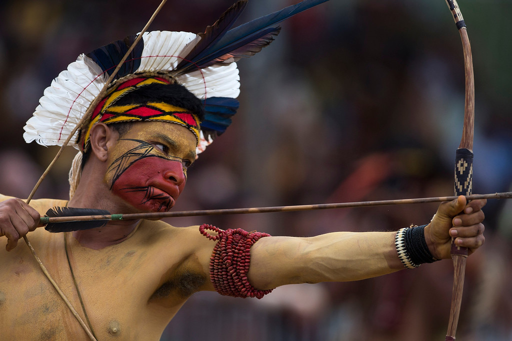 Description of . A Pataxo Indian takes part in the bow and arrow competition during the indigenous games in Cuiaba, Brazil, Tuesday, Nov. 12, 2013. Around 1,600 Indians from 48 tribes are celebrating Brazil's indigenous cultures during the 12th edition of the Games of the Indigenous People, which runs until Nov. 16. (AP Photo/Felipe Dana)