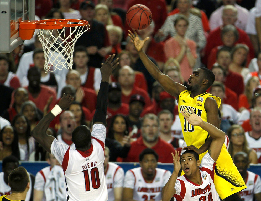 Description of . Michigan Wolverines guard Tim Hardaway Jr. (10) goes to the basket over Louisville Cardinals guard/forward Wayne Blackshear (20) and center Gorgui Dieng (10) of their NCAA men's Final Four championship basketball game in Atlanta, Georgia April 8, 2013. REUTERS/Tami Chappell