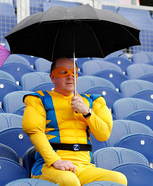 Description of . A cricket fan dressed with a superheroe outfit holds an umbrella as rain delays the start of play on the first day of the first Test cricket match between England and Sri Lanka at the Swalec Stadium in Cardiff, Wales, on May 26, 2011.   AFP PHOTO/ IAN KINGTON