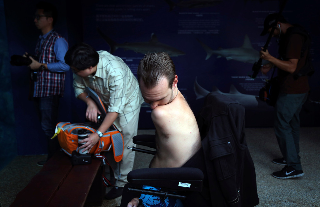 "Description of . Nick Vujicic wipes his nose with his shoulders while watching the sharks in an enclosure before diving with them Thursday, Sept. 5, 2013 in Singapore. Vujicic, a Serbian Australian evangelist and motivational speaker born with tetra-amelia syndrome, a rare disorder characterized by the absence of all four limbs, is in the city-state to give a motivational talk and was visiting ""The Shark Encounter at Marine Life Park\"" at one of Singapore\'s main tourist attractions in Resorts World Sentosa. (AP Photo/Wong Maye-E)"