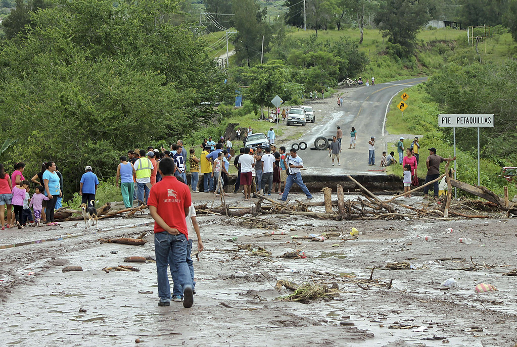 Description of . Residents stare at a bridge swept away by heavy rains in Chilpancingo, state of Guerrero, Mexico, on September 17, 2013. Mexican authorities scrambled Tuesday to launch an air lift to evacuate tens of thousands of tourists stranded amid floods in the resort of Acapulco following a pair of deadly storms. The official death toll rose to 47 after the tropical storms, Ingrid and Manuel, swarmed large swaths of the country during a three-day holiday weekend, sparking landslides and causing rivers to overflow in several states. EDUARDO GUERRERO/AFP/Getty Images