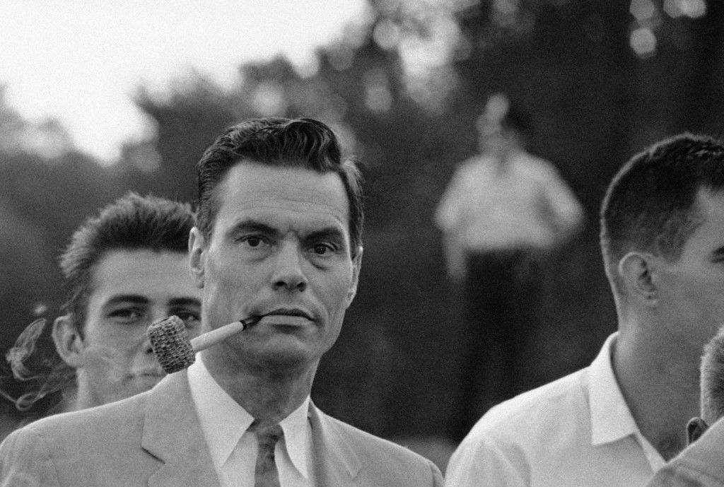 Description of . George Lincoln Rockwell, leader of the Anti-Negro Anti-Jew American Nazi Party, puffs on a corncob pipe as he poses at the Washington Monument, August 28, 1963, Rockwell and about 40 of his followers showed up without customary uniforms in the monument grounds, center of the March on Washington activities. Police denied a parade permit for Rockwell. (AP Photo)