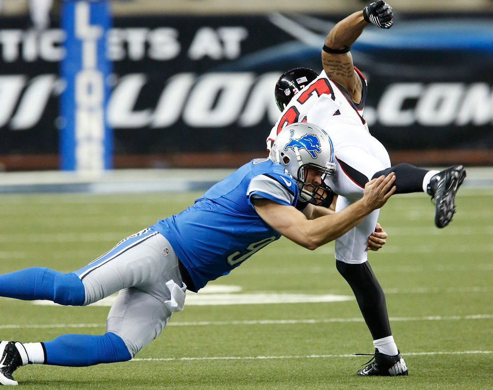 Description of . Detroit Lions quarterback Matthew Stafford tackles Atlanta Falcons cornerback Robert McClain (27) after McClain recovered a fumble by Lions receiver Calvin Johnson during the second quarter of an NFL football game at Ford Field in Detroit, Saturday, Dec. 22, 2012. (AP Photo/Duane Burleson)