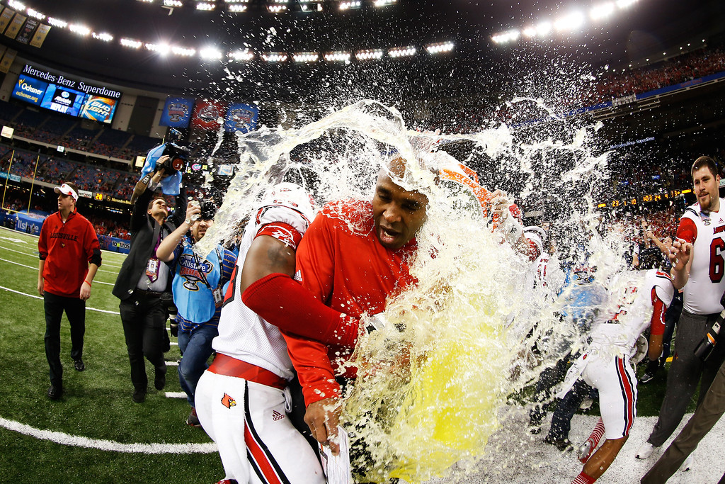 Description of . The Gatorade bucket is dumped on head coach Charlie Strong of the Louisville Cardinals after their 33 to 23 win over the Florida Gators in the Allstate Sugar Bowl at Mercedes-Benz Superdome on January 2, 2013 in New Orleans, Louisiana.  (Photo by Chris Graythen/Getty Images)