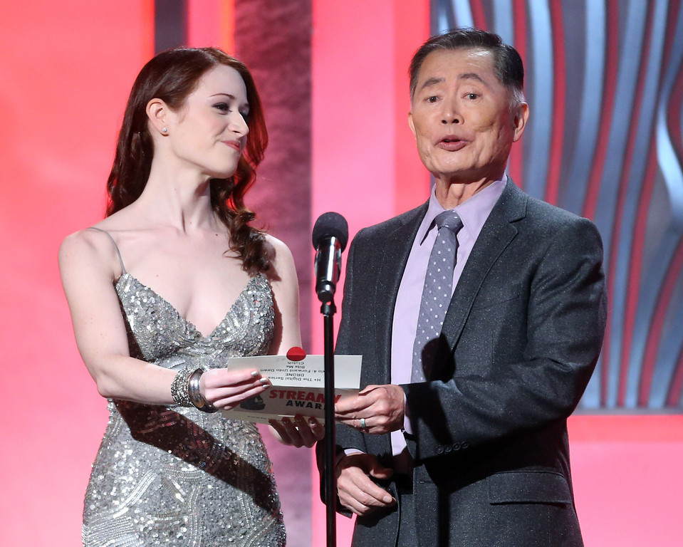 Description of . Presenters Ashley Clements (L) and George Takei speak onstage at the 3rd Annual Streamy Awards at Hollywood Palladium on February 17, 2013 in Hollywood, California.  (Photo by Frederick M. Brown/Getty Images)
