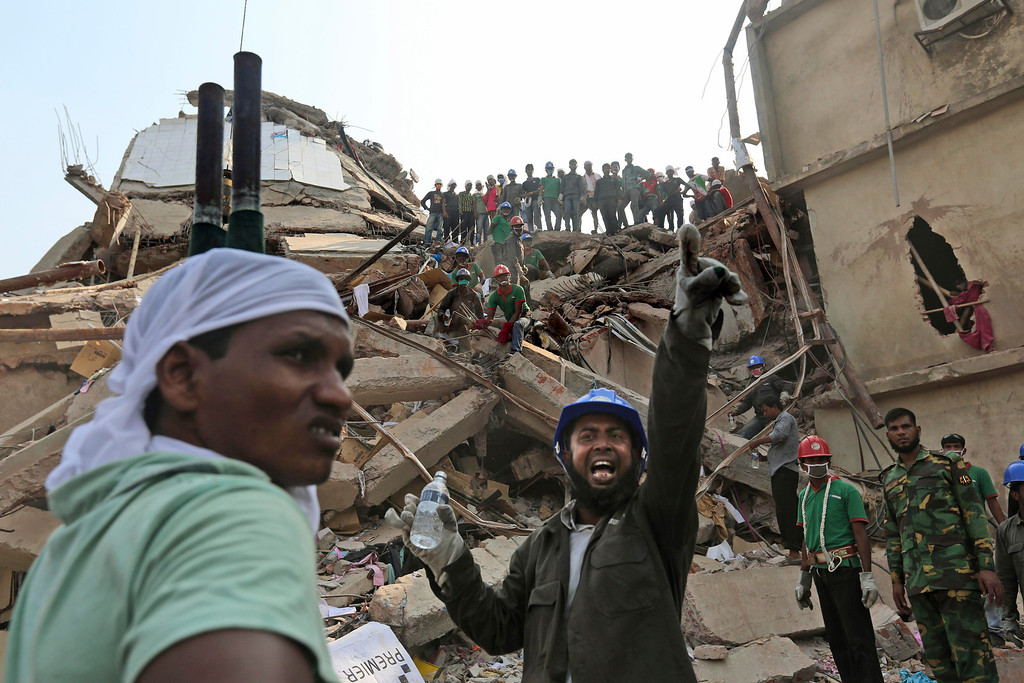 Description of . A Bangladeshi rescuer shouts for assistance as another waits with a stretcher for injured or dead at the site of a building that collapsed Wednesday in Savar, near Dhaka, Bangladesh, Thursday, April 25, 2013.  (AP Photo/Kevin Frayer)