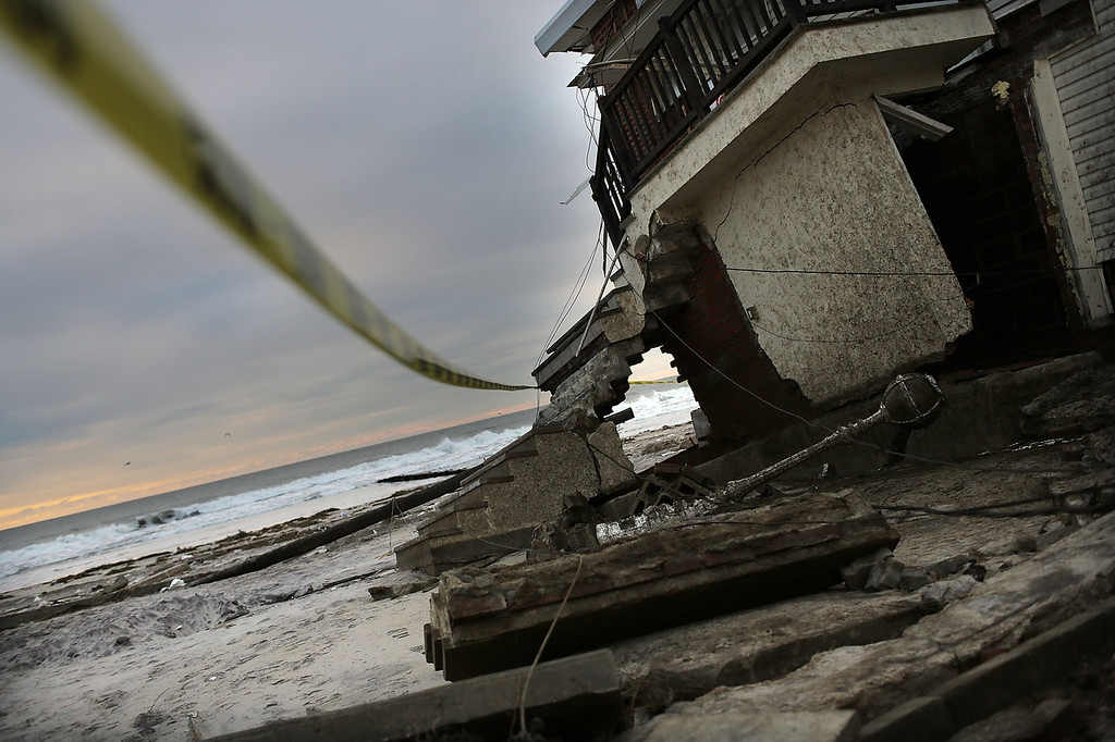 Description of . A damaged home is cordoned off along the beach in the Rockaway neighborhood, in Queens where a large section of the iconic boardwalk was washed away on November 2, 2012 in New York, United States. Limited public transit has returned to New York and most major bridges have reopened but will require three occupants in the vehicle to pass. With the death toll currently over 70 and millions of homes and businesses without power, the US east coast is attempting to recover from the effects of floods, fires and power outages brought on by superstorm Sandy.  (Photo by Spencer Platt/Getty Images)