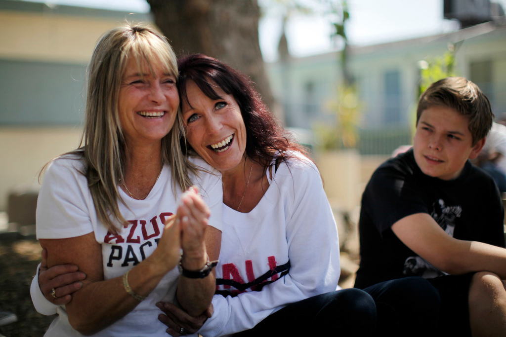 Description of . Tammy Fah, 48, (L) hugs Kathy Jamieson, 43, as they sit with Fah's son Matthew Stenger, 13,  at Prototypes residential treatment program in Pomona, California, March 26, 2013. Prototypes is part of the Second Chance Women's Re-entry Court program, one of the first in the U.S. to focus on women. It offers a cost-saving alternative to prison for women who plead guilty to non-violent crimes and volunteer for treatment. Of the 297 women who have been through the court since 2007, 100 have graduated, and only 35 have been returned to state prison. Picture taken March 26, 2013. REUTERS/Lucy Nicholson
