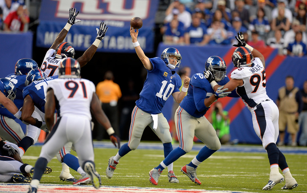 Description of . New York Giants quarterback Eli Manning (10) throws a pass downfield over the Denver Broncos defense during the second quarter September 15, 2013 MetLife Stadium. (Photo by John Leyba/The Denver Post)