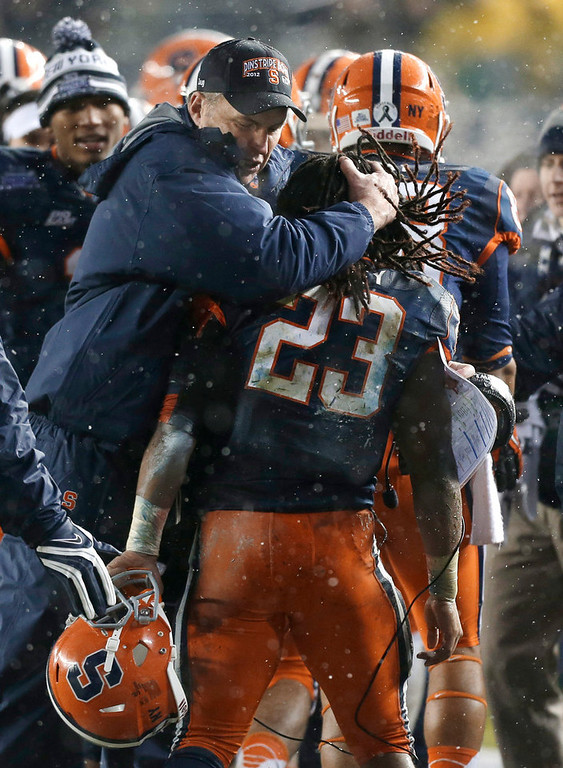 Description of . Syracuse coach Doug Marone embraces running back Prince-Tyson Gulley (23) who scored a second-quarter touchdown against West Virginia during the Pinstripe Bowl NCAA college football game at Yankee Stadium in New York, Saturday, Dec. 29, 2012. (AP Photo/Kathy Willens)