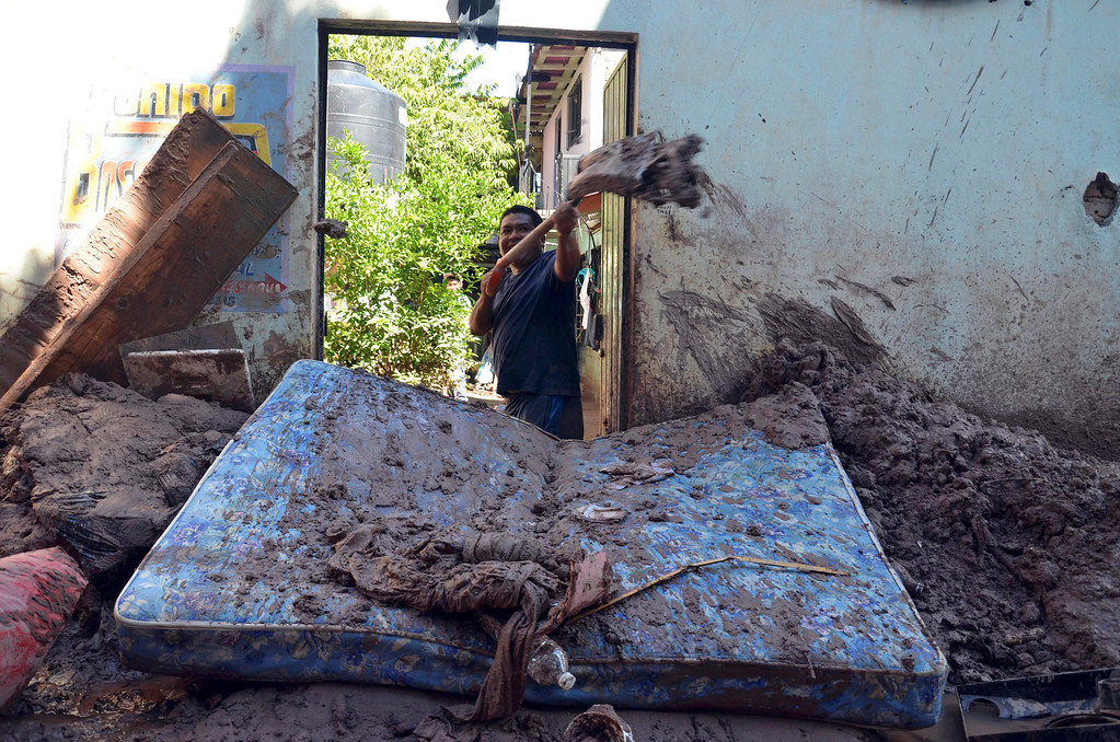 Description of . A man shovels mud from his home after flooding brought by Tropical Storm Manuel in Chilpancingo, Mexico, Thursday, Sept. 19, 2013.   (AP Photo/Alejandrino Gonzalez)