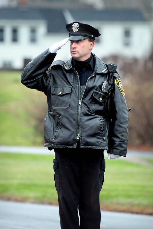 Description of . A member of the Norwalk Police Dept. salutes as the funeral procession for six-year-old Jack Pinto, a victim of the Sandy Hook Elementary School shootings, travels down Main St. in Newtown on 12/17/2012. Photo by Arnold Gold/New Haven Register