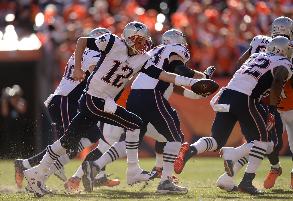 Description of . New England Patriots quarterback Tom Brady (12) hands off during the first quarter. The Denver Broncos take on the New England Patriots in the AFC Championship game at Sports Authority Field at Mile High in Denver on January 19, 2014. (Photo by Hyoung Chang/The Denver Post)