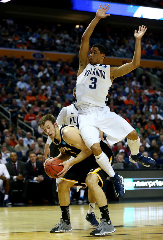 Description of . BUFFALO, NY - MARCH 20: Josh Hart #3 of the Villanova Wildcats collides with Kyle Kelm #3 of the Milwaukee Panthers during the second round of the 2014 NCAA Men's Basketball Tournament at the First Niagara Center on March 20, 2014 in Buffalo, New York.  (Photo by Elsa/Getty Images)