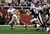 Eli Manning #10 of the New York Giants scrambles away from th New England Patriots defense to throw a 32 yard pass to David Tyree #85 of the Giants during the four quarter of Super Bowl XLII on February 3, 2008 at the University of Phoenix Stadium in Glendale, Arizona.  (Photo by Andy Lyons/Getty Images)