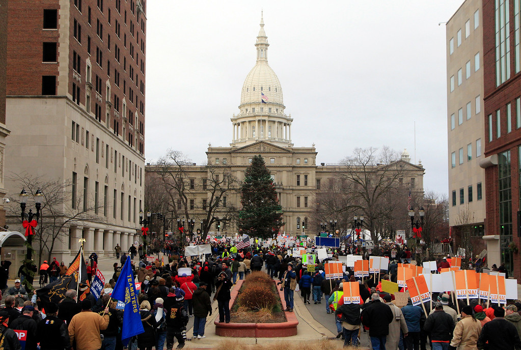Description of . Thousands of supporter march to the State Capitol grounds in Lansing, Mich., Tuesday, Dec. 11, 2012. The crowd is protesting right-to-work legislation that was passed by the state legislature last week.  (AP Photo/Carlos Osorio)