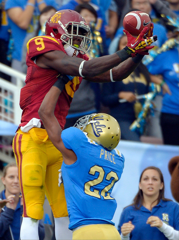 Description of . Southern California wide receiver Marqise Lee, left, can't hold on to a pass in the end zone as UCLA cornerback Sheldon Price defends during the first half of their NCAA college football game, Saturday, Nov. 17, 2012, in Pasadena, Calif. Price was called for pass interference on the play. (AP Photo/Mark J. Terrill)