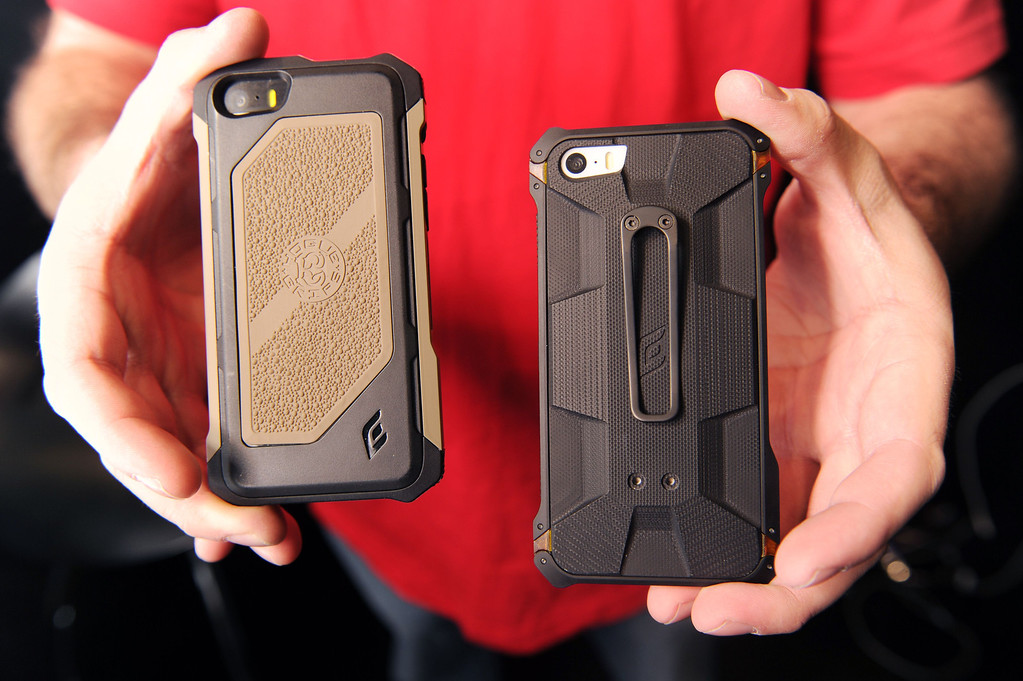 Description of . The Rogue Black Ops iPhone case (L) and the Sector 5 Black Ops Elite iPhone case (R) are displayed at the 2014 International CES in Las Vegas, Nevada, January 8, 2014.  The Sector 5, Black Ops Elite, the new flagship case in manufacturer's Element Case Tactical line, is made from G10 - a shock-absorbing polymer material used in its military spec gun grips, and costs USD $219.99.  The Rogue Black Ops is made from durable aluminum and carbon fiber and costs USD $119.99. AFP PHOTO / Robyn Beck/AFP/Getty Images