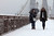 Women walk on the Brooklyn Bridge during a snowstorm in New York, March 8, 2013.  REUTERS/Eduardo Munoz