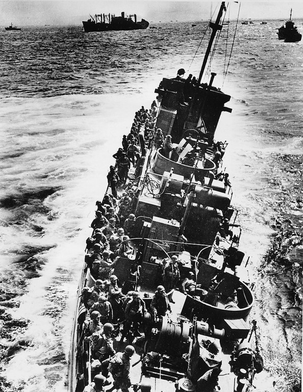 Description of . A U.S. Coast Guard LCI, heavily listing to port, moves alongside a transport ship to evacuate her troops, during the initial Normandy landing operations in France, on June 6, 1944. Moments later the craft will capsize and sink. Note that helmeted infantrymen, with full packs, are all standing to starboard side of the ship. (AP Photo)