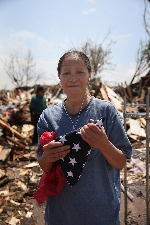Description of . MOORE, OK - MAY 23:  Kriket Krekemeyer holds the burial flag of her father, who was a career Navy man, after it was recovered from her destroyed home on May 23, 2013 in Moore, Oklahoma. The flag was one of the most important possessions she had hoped to recover from the rubble that was once her home. A two-mile wide EF5 tornado touched down in Moore May 20 killing at least 24 people and leaving behind extensive damage to homes and businesses. U.S. President Barack Obama promised federal aid to supplement state and local recovery efforts.  (Photo by Scott Olson/Getty Images)