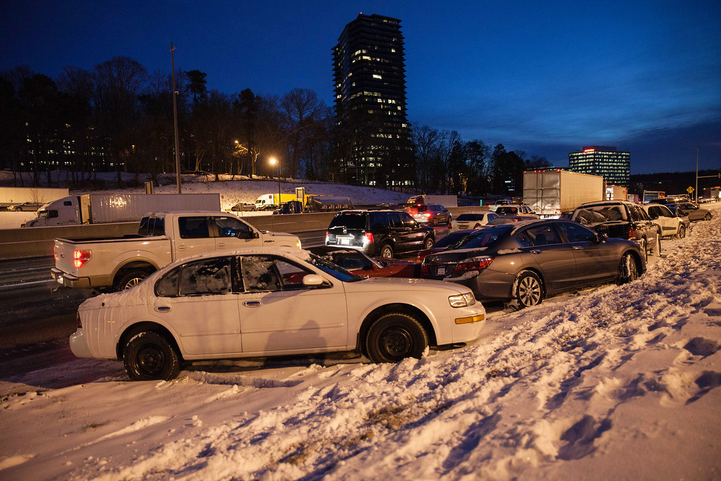 Description of . Abandoned vehicles line  I-285 early Wednesday, Jan. 29, 2014, in Dunwoody, Ga., after a rare  winter storm hit Georgia.  While such amounts barely qualify as a storm in the north, it was enough to paralyze the Deep South.  (AP Photo/Branden Camp)