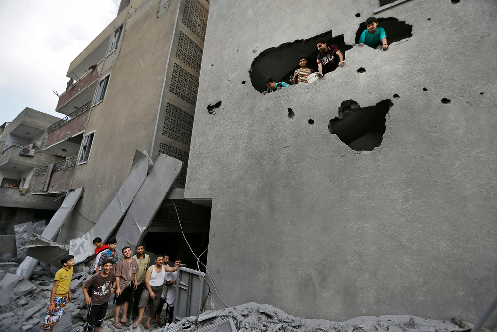 Description of . Palestinians from a damaged apartment building inspect the damage to a neighboring building, the offices of the Hamas movement's Al-Aqsa satellite TV station, in Gaza City, northern Gaza Strip, destroyed by an Israeli strike, Tuesday, July 29, 2014. Early Tuesday, Israel warplanes struck a series of targets in Gaza City, including the top Hamas leader in Gaza, Ismail Haniyeh's house and government offices, while Gaza's border area with Israel was hit by heavy tank shelling. (AP Photo/Lefteris Pitarakis)