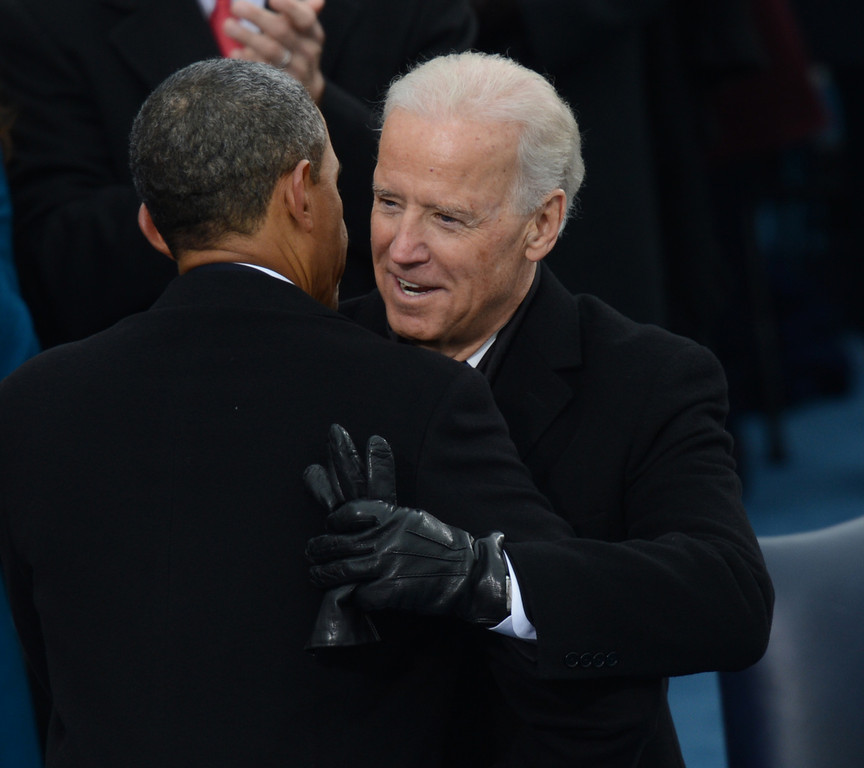 Description of . US President Barack Obama(L) embraces US Vice President Joe Biden after taking the oath of office during the 57th Presidential Inauguration ceremonial swearing-in at the US Capitol on January 21, 2013 in Washington, DC. The oath was administered by US Supreme Court Chief Justice John Roberts, Jr.  SAUL LOEB/AFP/Getty Images