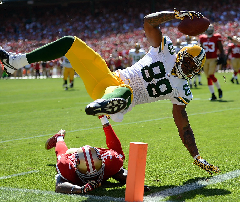 Description of . Jermichael Finley #88 of the Green Bay Packers scores on a twelve yard pass play diving over the tackle of Donte Whitner #31 of the  San Francisco 49ers during the second quarter at Candlestick Park on September 8, 2013 in San Francisco, California.  (Photo by Thearon W. Henderson/Getty Images)