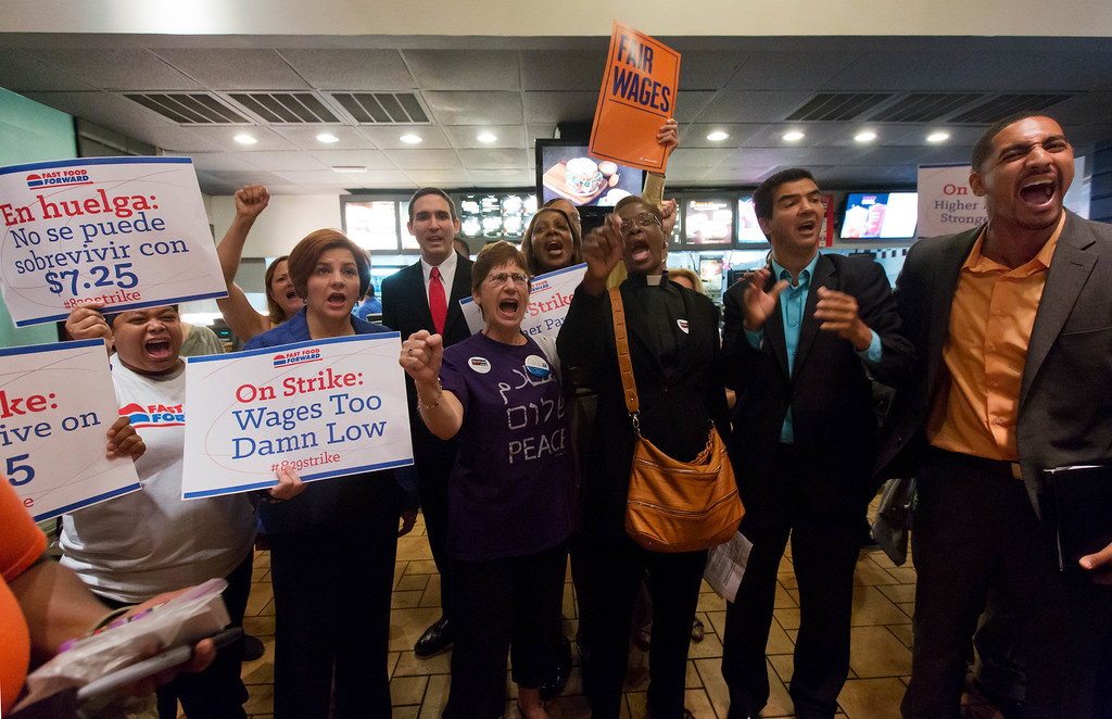 Description of . Protesting fast food workers, joined by New York City Council Speaker and mayoral candidate Christine Quinn, second left, and protest organizers, chant inside a McDonald's restaurant on New York's Fifth Avenue,  Thursday, Aug. 29, 2013.  (AP Photo/Richard Drew)