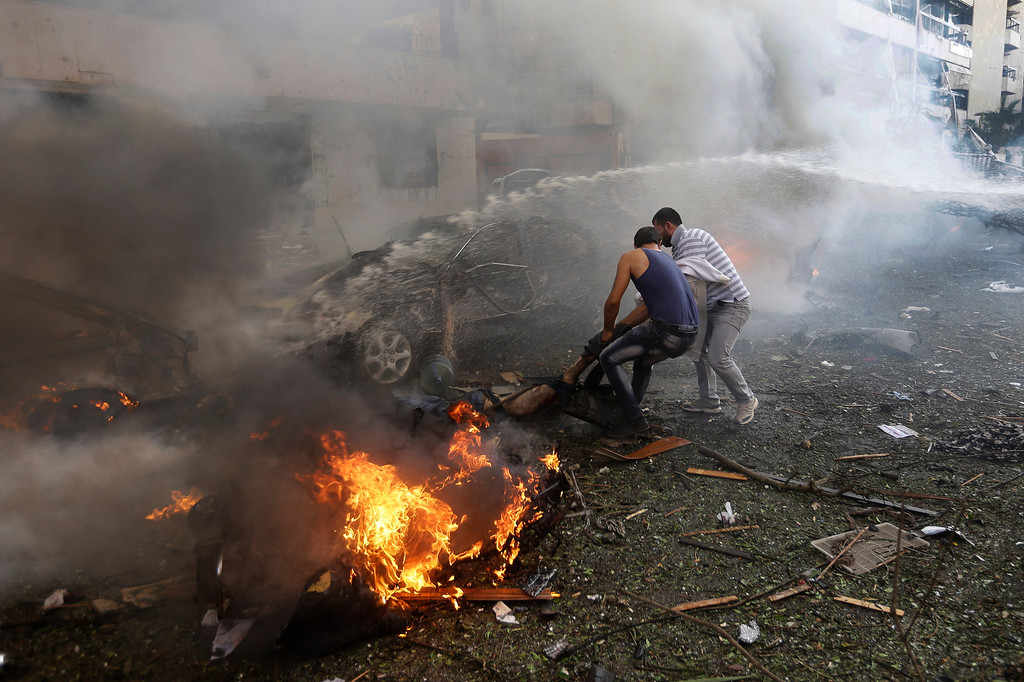 Description of . Lebanese men remove a dead body from a burned car, at the scene where two explosions have struck near the Iranian Embassy killing many, in Beirut, Lebanon, Tuesday Nov. 19, 2013. The blasts in south Beirut\'s neighborhood of Janah also caused extensive damage on the nearby buildings and the Iranian mission. The area is a stronghold of the militant Hezbollah group, which is a main ally of Syrian President Bashar Assad in the civil war next door. It\'s not clear if the blasts are related to Syria\'s civil war. (AP Photo/Hussein Malla)
