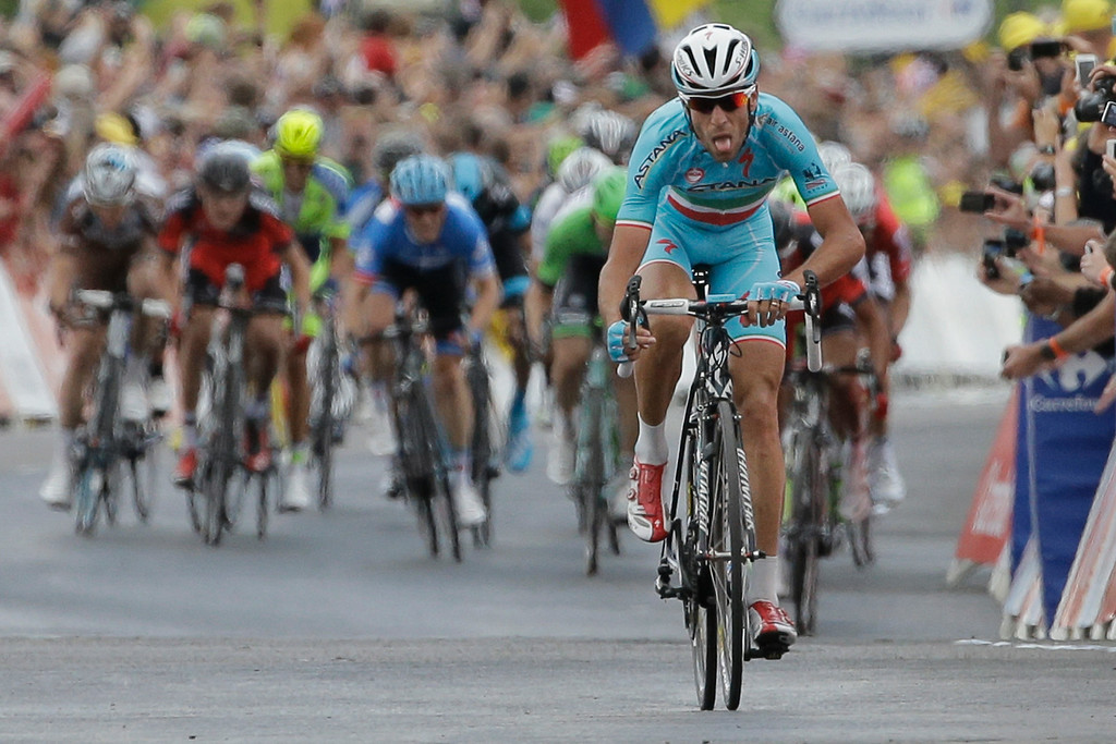 Description of . Italy's Vincenzo Nibali grimaces as he strains to stay ahead of the sprinting pack, rear, to win the second stage of the Tour de France cycling race over 201 kilometers (124.9 miles) with start in York and finish in Sheffield, England, Sunday, July 6, 2014. (AP Photo/Laurent Cipriani)