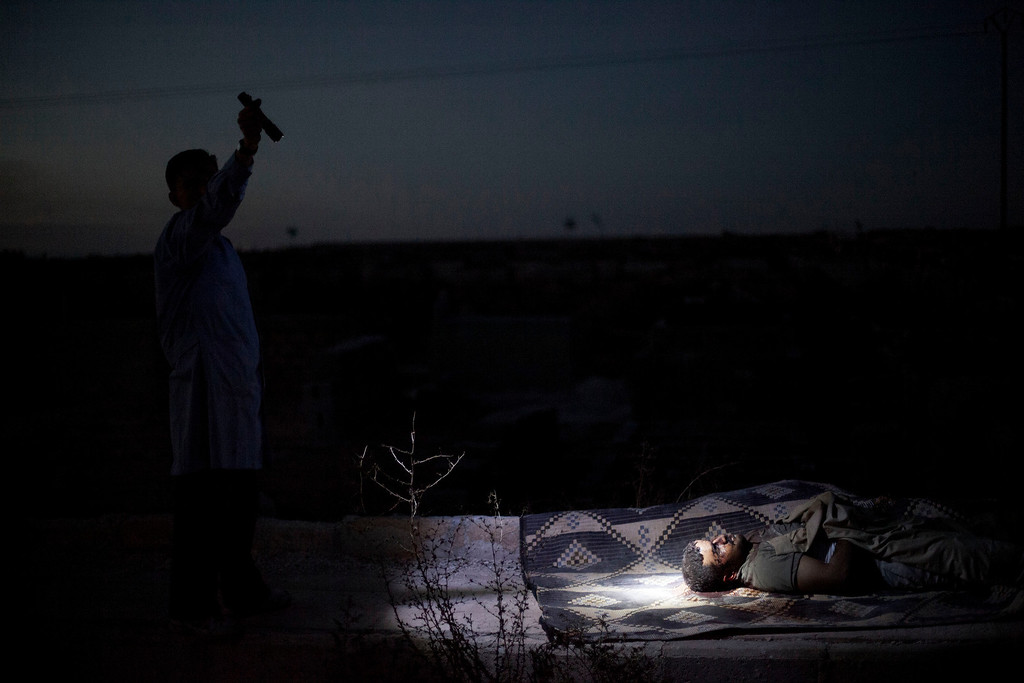 Description of . FILE - A man points a flashlight toward the body of a Syrian man killed from Syrian Army shelling at a graveyard in Aleppo, Syria, Saturday, Oct. 13, 2012. (AP Photo/Manu Brabo, File)
