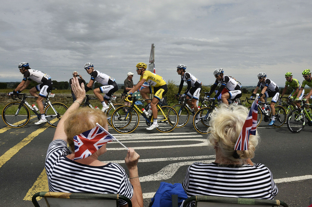 Description of . Supporters wave along the road as Germany's Marcel Kittel (C), wearing the overall leader's yellow jersey, rides past during the 201 km second stage of the 101th edition of the Tour de France cycling race on July 6, 2014 between York and Sheffield, northern England.  AFP PHOTO / JEFF PACHOUDJEFF PACHOUD/AFP/Getty Images