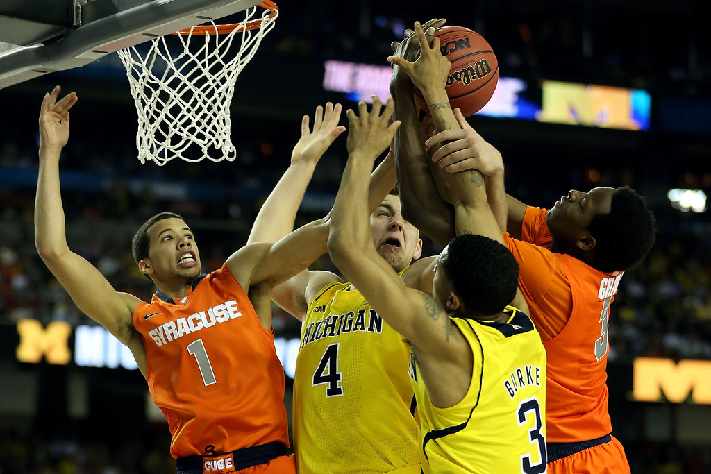 Description of . ATLANTA, GA - APRIL 06:  Michael Carter-Williams (L) #1 and Jerami Grant #3 (R) of the Syracuse Orange fight for a rebound in the second half against Mitch McGary #4 and Trey Burke #3 of the Michigan Wolverines during the 2013 NCAA Men's Final Four Semifinal at the Georgia Dome on April 6, 2013 in Atlanta, Georgia.  (Photo by Streeter Lecka/Getty Images)