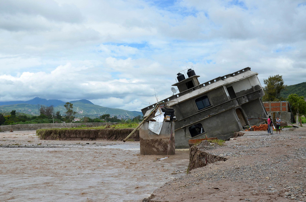 Description of . People stand next to home collapsed into the Huacapa River overflowed due to heavy rains caused by Tropical Storm Manuel near the town of Petaquillas, Mexico, Tuesday, Sept. 17, 2013. Twin storms left scenes of havoc on both of Mexico's coasts on Tuesday, with tens of thousands of tourists stranded in resort city of Acapulco on the Pacific and heavy damage reported along the Gulf coast. (AP Photo/Alejandrino Gonzalez)