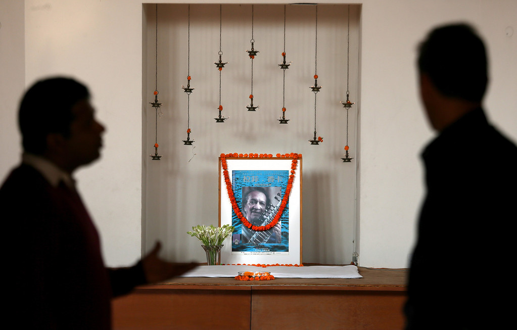 . Indians talk near the photograph of legendary Indian sitar player Ravi Shankar at his music center, in New Delhi, India, Wednesday, Dec. 12, 2012. Shankar, who is credited with connecting the world to Indian music, died Tuesday in San Diego at the age of 92. (AP Photo/ Manish Swarup)