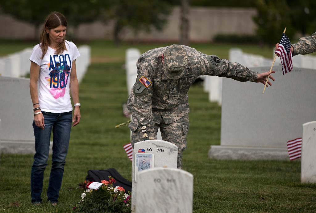 """Description of . Jennifer Henderson, of Winston-Salem, N.C., watches as Col. Jim Market, of the 3rd U.S. Infantry Regiment, also known as The Old Guard, places a flag at the grave site of her husband Sgt. 1st Class Christopher Henderson, who was killed in Afghanistan on June 17, 2007, at Arlington National Cemetery as part of the annual \""""Flags-In\"""" ceremony in preparation for Memorial Day on Thursday, May 23, 2013, in Arlington, Va. (AP Photo/Evan Vucci)"""