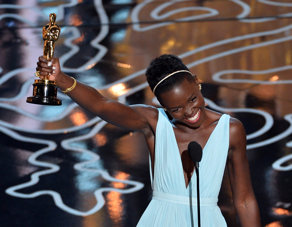 Description of . Actress Lupita Nyong'o accepts the Best Performance by an Actress in a Supporting Role award for '12 Years a Slave' onstage during the Oscars at the Dolby Theatre on March 2, 2014 in Hollywood, California.  (Photo by Kevin Winter/Getty Images)