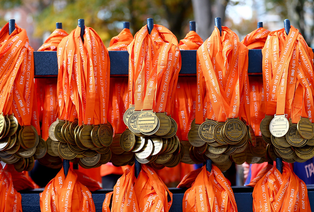 Description of . Medals are distributed for participants beyond the finish line of the the 2013 ING New York City Marathon on November 3, 2013 in New York City.  (Photo by Elsa/Getty Images)