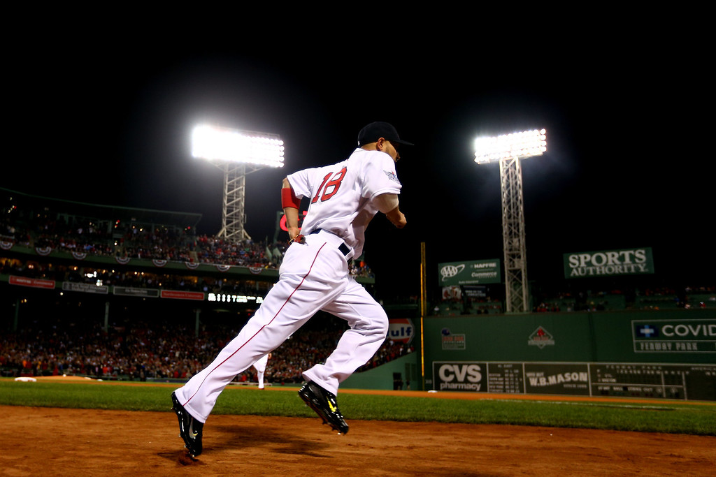 Description of . Shane Victorino #18 of the Boston Red Sox takes the field for the start of Game One of the 2013 World Series against the St. Louis Cardinals at Fenway Park on October 23, 2013 in Boston, Massachusetts.  (Photo by Elsa/Getty Images)