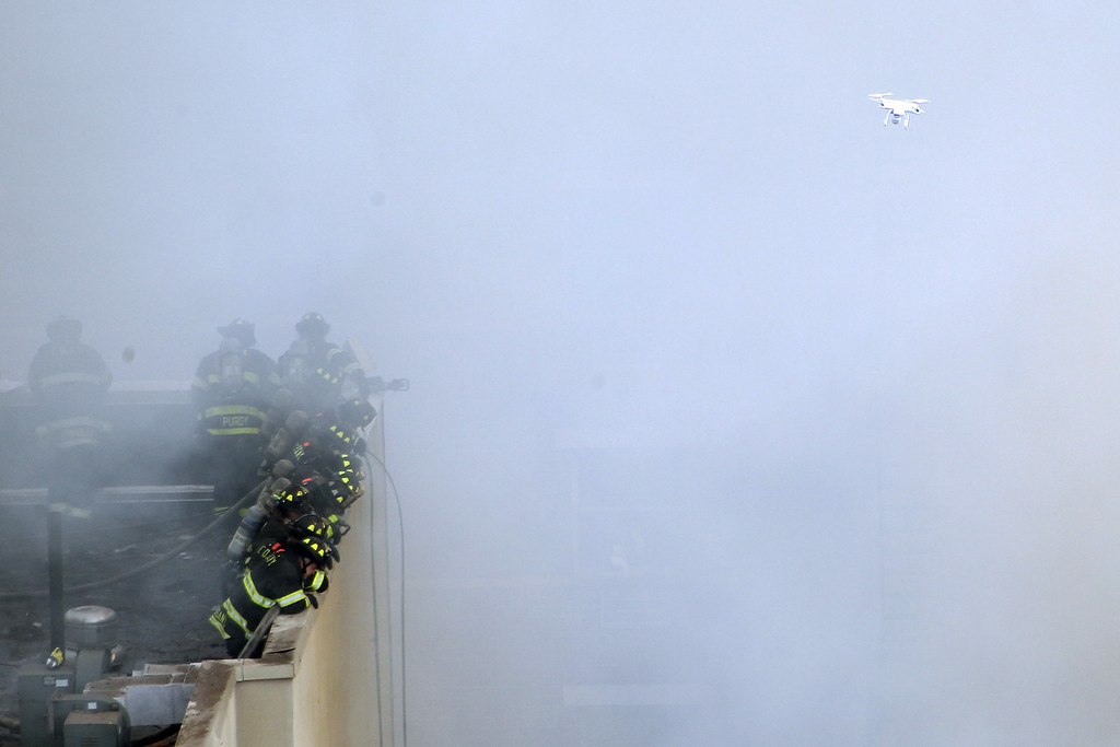 Description of . Firefighters from the Fire Department of New York (FDNY) respond to a five-alarm fire and building collapse at 1646 Park Ave as a drone flies overheard in the Harlem neighborhood of Manhattan March 12, 2014 in New York City.   (Photo by Justin Heiman/Getty Images)