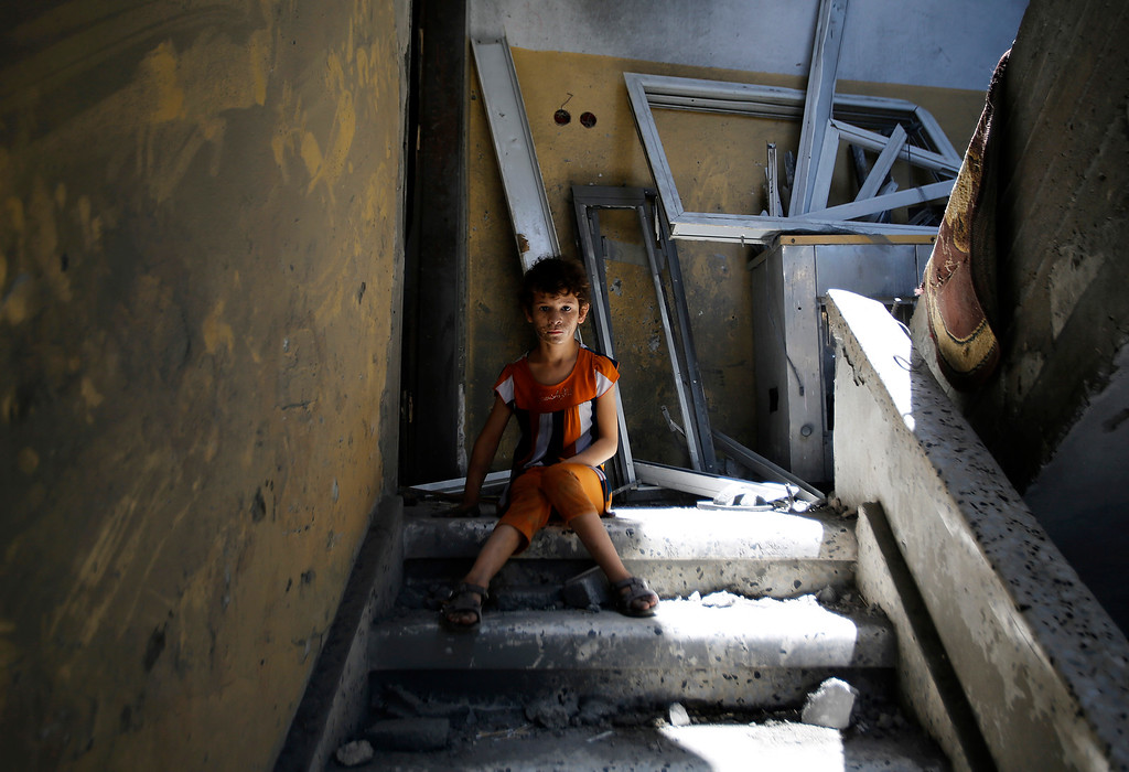 Description of . A Palestinian boy sits in the stairwell of his home in the heavily bombed Gaza City neighborhood of Shijaiyah, close to the Israeli border, Friday, Aug. 1, 2014. A three-day Gaza cease-fire that began Friday quickly unraveled, with Israel and Hamas accusing each other of violating the truce. (AP Photo/Hatem Moussa)