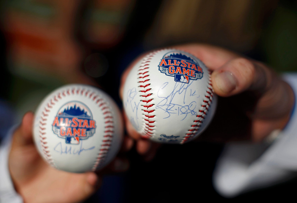 Description of . Fans hold autographed baseballs ahead of Major League Baseball's All-Star Game in New York, July 16 2013. REUTERS/Mike Segar