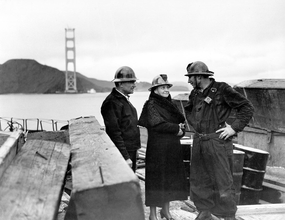 Description of . U.S. Secretary of Labor Frances Perkins, center, wears a steel helmet during an inspection tour of the San Francisco tower of the Golden Gate Bridge, Ca., March 25, 1935.  Perkins, who is the first female cabinet officer in American history, talks with G.A. McClain, bridge superintendent, left, and S.E. Stanley, rivet foreman. (AP Photo)