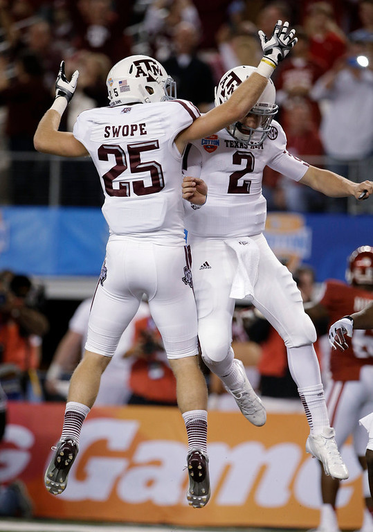 Description of . Texas A&M's Ryan Swope (25) and Johnny Manziel (2) celebrate a touchdown run by Manziel against Oklahoma in the first half of the Cotton Bowl NCAA college football game Friday, Jan. 4, 2013, in Arlington, Texas. (AP Photo/Tony Gutierrez)