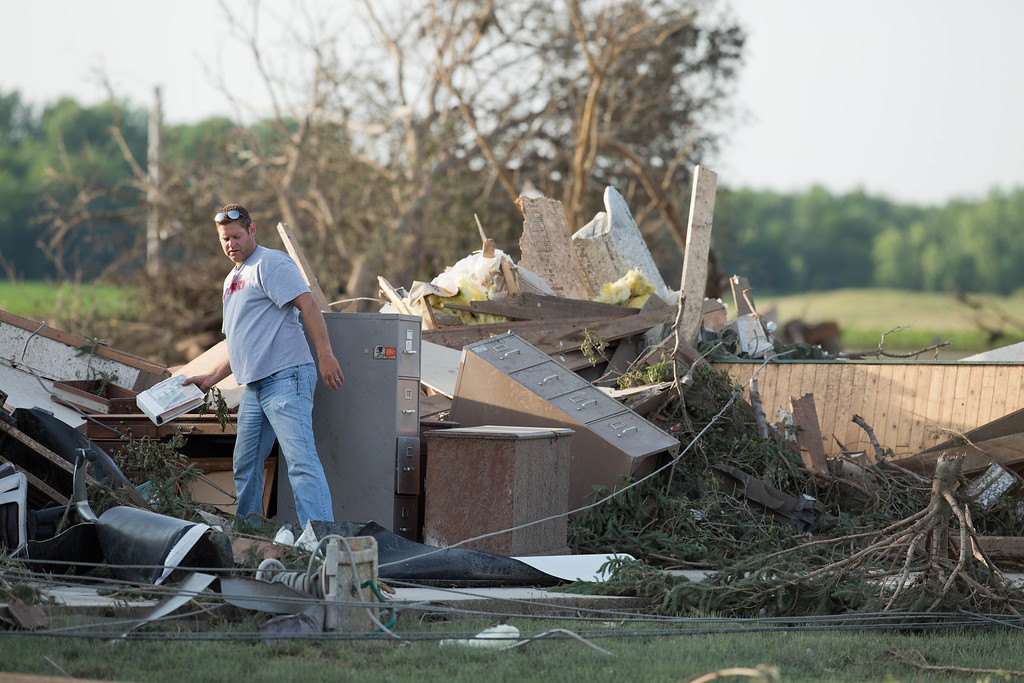 Description of . A person looks through the remains of a building in Pilger, Neb.,  on Tuesday morning, June 17, 2014. The National Weather Service says the storm that struck northeast Nebraska appears to have produced four tornadoes, one of which ravaged the town of Pilger.   (AP Photo/The World-Herald, Ryan Soderlin)