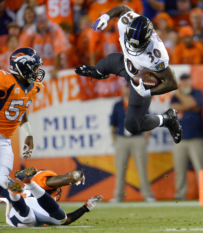 Description of . Baltimore Ravens running back Bernard Pierce (30) leaps over a Bronco defender for a gain in the first quarter.  (Photo by Joe Amon/The Denver Post)