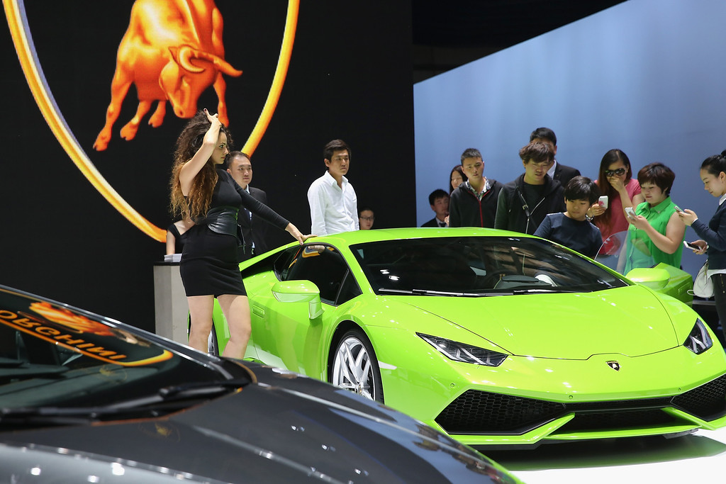 Description of . The potential consumers look at a Lamborghini sport car during the 2014 Beijing International Automotive Exhibition at China International Exhibition Center on April 21, 2014 in Beijing, China.  (Photo by Feng Li/Getty Images)