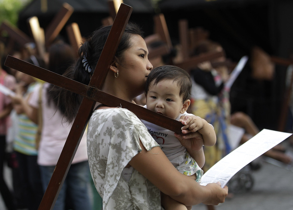 Description of . A Filipino child bites a wooden cross as devotees practice different religious rites during the Holy Week at the Philippine Center of Saint Pio of Pietrelcina on Thursday, March 28, 2013 in suburban Quezon city, east of Manila, Philippines.(AP Photo/Aaron Favila)